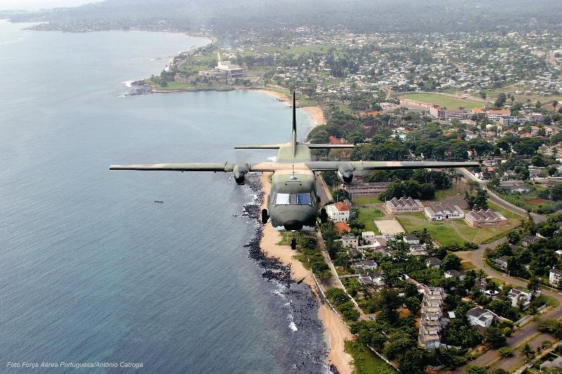 O C-212-100 AVIOCAR a sobrevoar a avenida marginal da cidade de S. Tomé