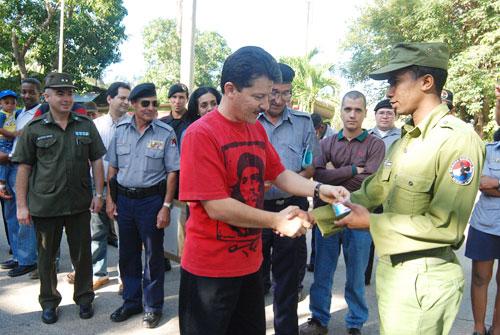 Um agente da BRIGADA ESPECIAL NACIONAL é agraciado pelas autoridades políticas. (Foto de «Granma»)