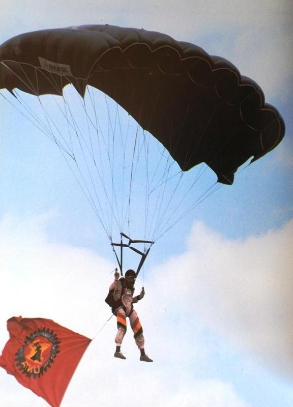 Pára-quedista da FAPA-DAA durante um salto de demonstração durante um comício da UNIÃO NACIONAL DOS TRABALHADORES DE ANGOLA-UNTA. (Foto extraída do livro «FAPLA-Baluarte da paz em Angola»)