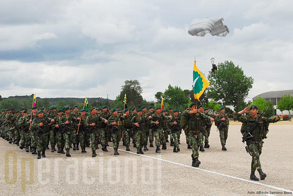 """O 1º Batalhão de Infantaria Pára-quedista desfila em """"frente 10"""" ao mesmo tempo que o Destacamento de Precursores, lançado a partir de um C-212 AVIOCAR, começa a chegar ao solo."""