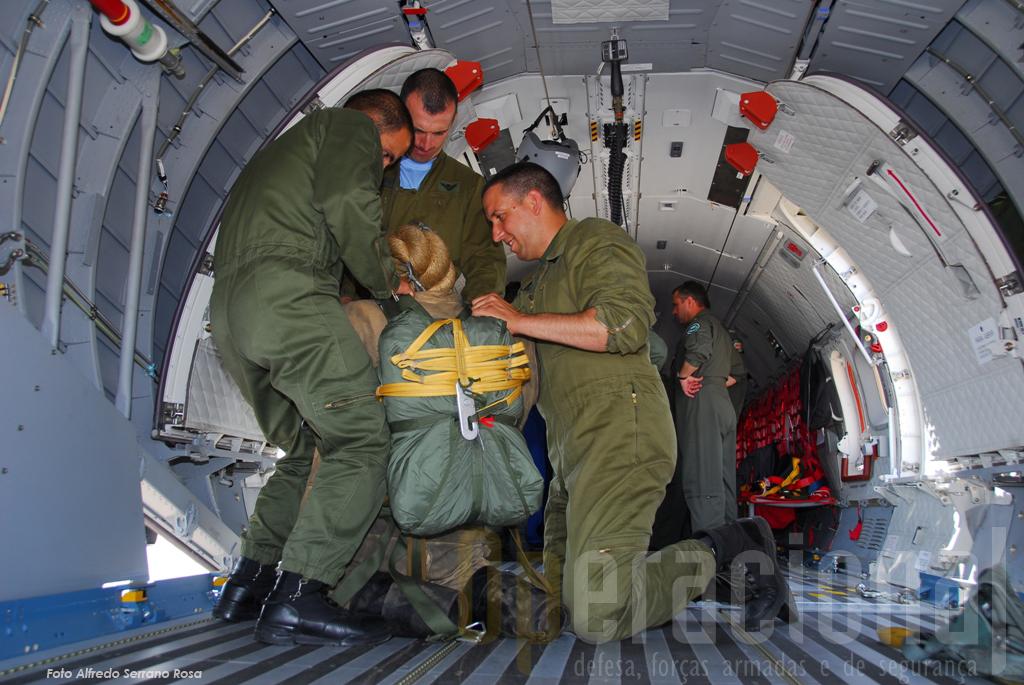 """Como é habitual quando se testa um novo pára-quedas ou avião, antes do homem, """"salta"""" um manequim. Aqui, ainda em terra, os instrutores equipam-no com um pára-quedas automático."""