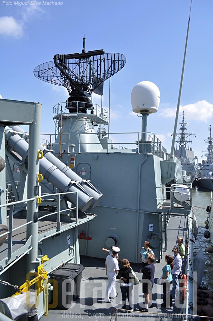 """À esquerda dos visitantes, os """"Harpoon"""", em cima uma das antenas INMARSAT e o LW08 e no seguimento os contentores dos misseis """"Sea Sparrow"""". São 16, oito em cada bordo, destinados à defesa anti-aérea de curto alcance (até 8 milhas) e são disparados verticalmente."""