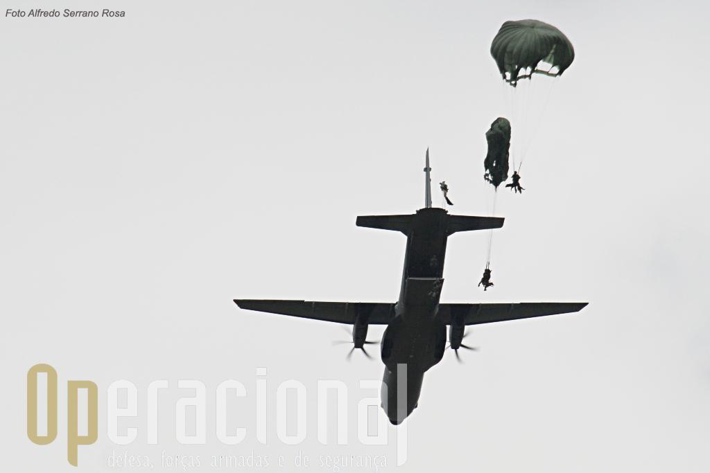 """A 1.500 pés de altitude, luz verde e...Já! Os pára-quedistas lançam-se no espaço. Na saída da aeronave o cã está """"junto"""" ao pára-quedista."""