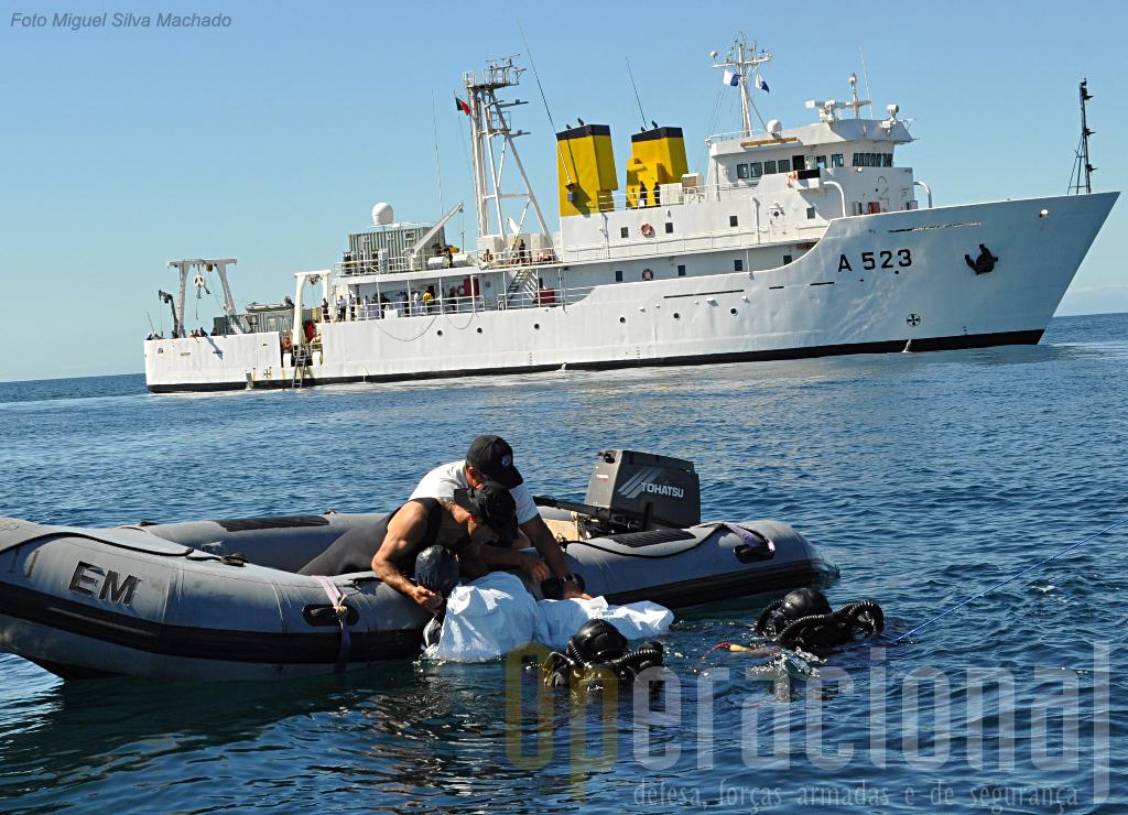 O (pesado) manequim que simulava o piloto preso ao helicópetro afundado acaba de ser trazido à superficie e colocdo num bote de apoio.