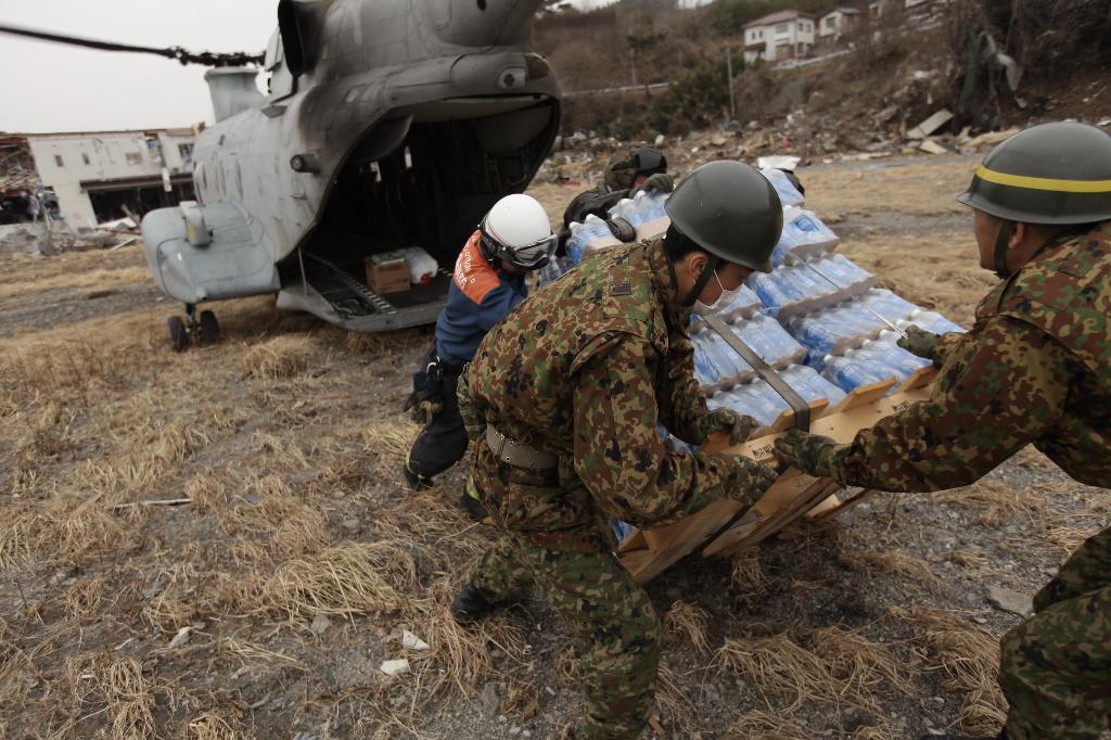 """Um CH-46E """"Sea Knight"""" do 265.º Esquadrão de Helicópteros Médios dos US Marines da base de Futenma em Okinawa, aqui no Nordeste do Japão no âmbito da operação """"Tomodachi"""" (Fotografia do U.S. Marine Corps pelo Lance Cpl. Ethan Johnson)."""