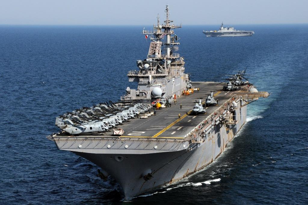 """Em primeiro plano o USS """"Essex"""" ao largo da costa Nordest do Japão, ao fundo o JS """"Hyuga"""" da Força Naval de Auto-Defesa do Japão. Os meios navais de grande capacidade de transporte e dispondo de helicópetros tiveram um papel de relevo nas operações de socorro (Foto US Navy)"""