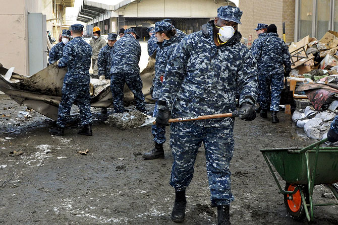 """Muito do apoio às populações passou pela """"força de braços"""". Aqui marinheiros americanos ajudam à limpeza de uma zona afectada em Hachinohe (Foto U.S. Navy pelo Petty Officer 2nd Class Devon Dow)."""