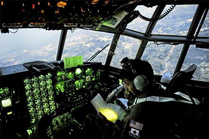 O capitão Yuri Batten da Força Aérea dos EUA aos comandos de um C-130 no decurso de uma missão de transporte de medicamentos em 19 de Março de 2011 (Foto US Air Foce pelo Staff Sgt. Jonathan Steffen).