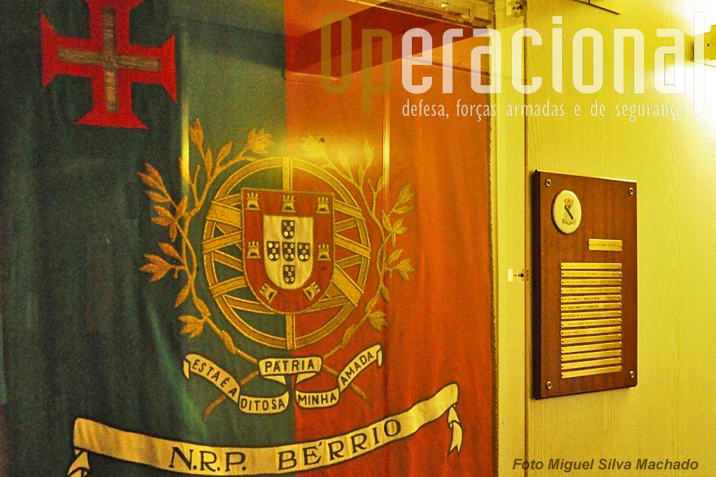 """O Estandarte Nacional do NRP """"Bérrio"""" exposto a bordo, junto à listagem com os nomes dos comandantes do navio."""