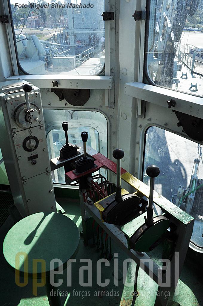 Sentado neste banco, controlando os guinchos com estes manobradores coloridos - operação que requer muito treino e jeito - está uma praça que assegura que as mangueiras cheguem ao local certo do outro navio.