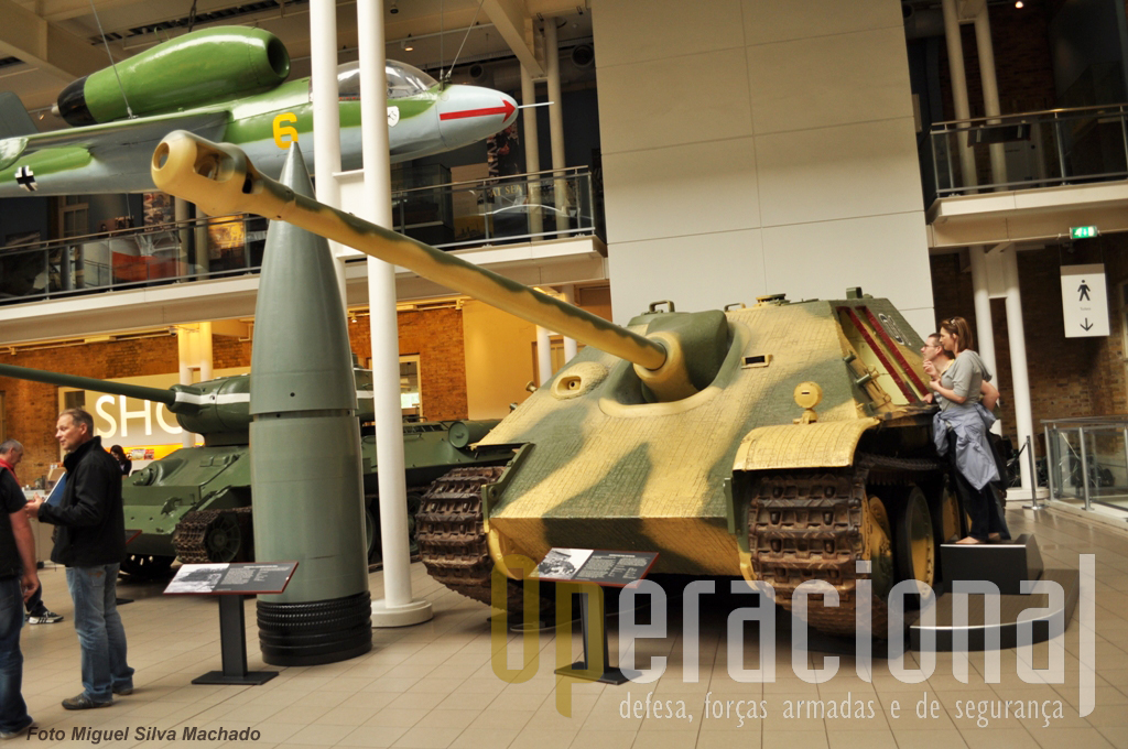 """À esquerda (cor cinzenta) o impressionante projectil do canhão sobre carris """"Schwerer Gustav"""" (Pesado Gustavo), de 80cm de calibre e 4.800 kg de peso. Este exemplar veio da fábrica (Krupp) em 1947. O blindado é um """"Jagdpanther"""" alemão usado na 2.ª Guerra Mundial, versão posto de comando e chegou ao museu em 1969 depois de ter estado em unidades inglesas para avaliação e depósito."""