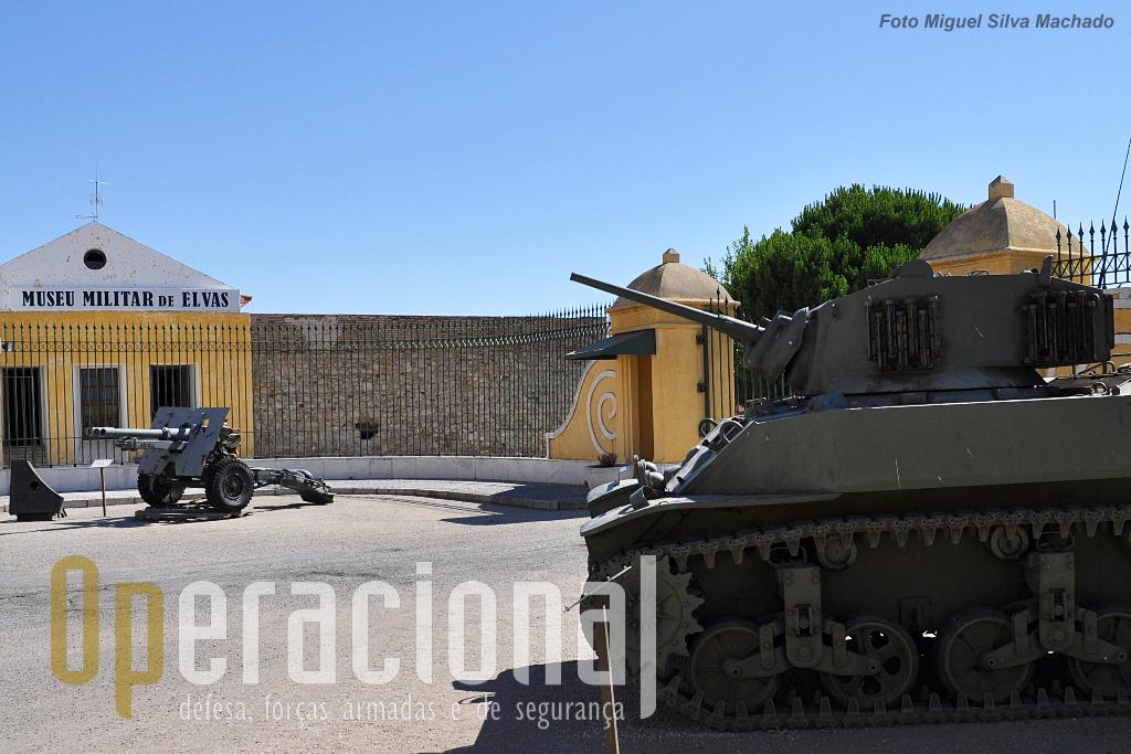 """Carro de combate M5A1 """"Stuart"""", modelo 1942 (origem, Canadá), celebrizado em Portugal através do livro """"Elefante DunDum"""" que  relata o seu serviço em Angola (Nambuangongo). Em fundo o obus 8,8cm, modelo 1943-46, temível na 2.ª Guerra Mundial como arma anti-carro,  as suas munições perfuravam, a 1.000m, blindagens com 162mm (como se comprova pela placa junto)."""