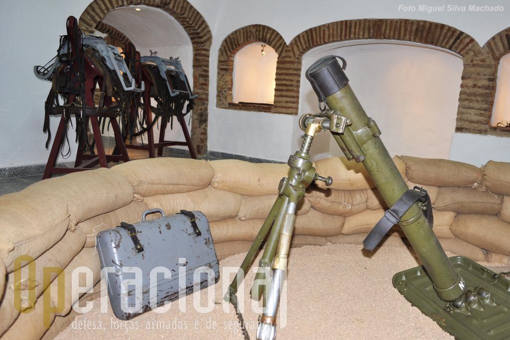 """8.Morteiro 81mm M/1937 (arma completa pesa 62,5 Kg), tendo junto a si um dos dois contentores porta-munições que os animais carregavam. Em segundo plano o """"arreio modelo 1939 de cavalo ou garrano para transporte de morteiro 8cm modelo 1937"""" e o mesmo arreio mas modelo para transporte de munições."""