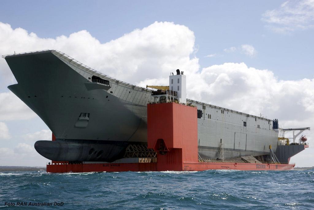 """A bordo do Blue Marlin, o casco do HMAS Canberra chega à Austrália. Observem-se os dois """"thrusters"""" na proa."""