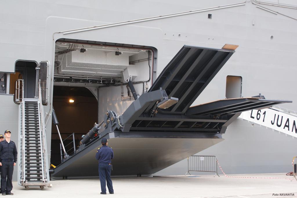 Uma das portas laterais do Juan Carlos I sendo aberta, formando uma rampa de acesso à garagem inferior, capaz de suportar o peso de carros de combate pesados.