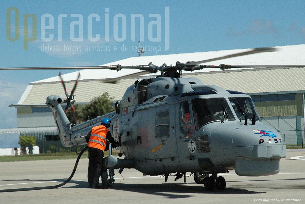 Sem parar motores, sob a vigilância dos bombeiros, o helicóptero é atestado com combustível sob pressão. Em poucos minutos está outra vez no ar.