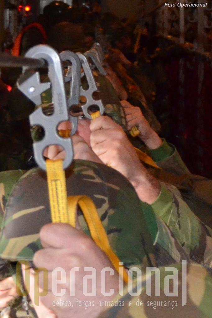"""Os """"fechos de enganchar"""" ligam o pára-quedas ao """"cabo de ancoragem"""". Quando o militar se lança no espaço é isto que permite a """"abertura automática"""" do pára-quedas."""