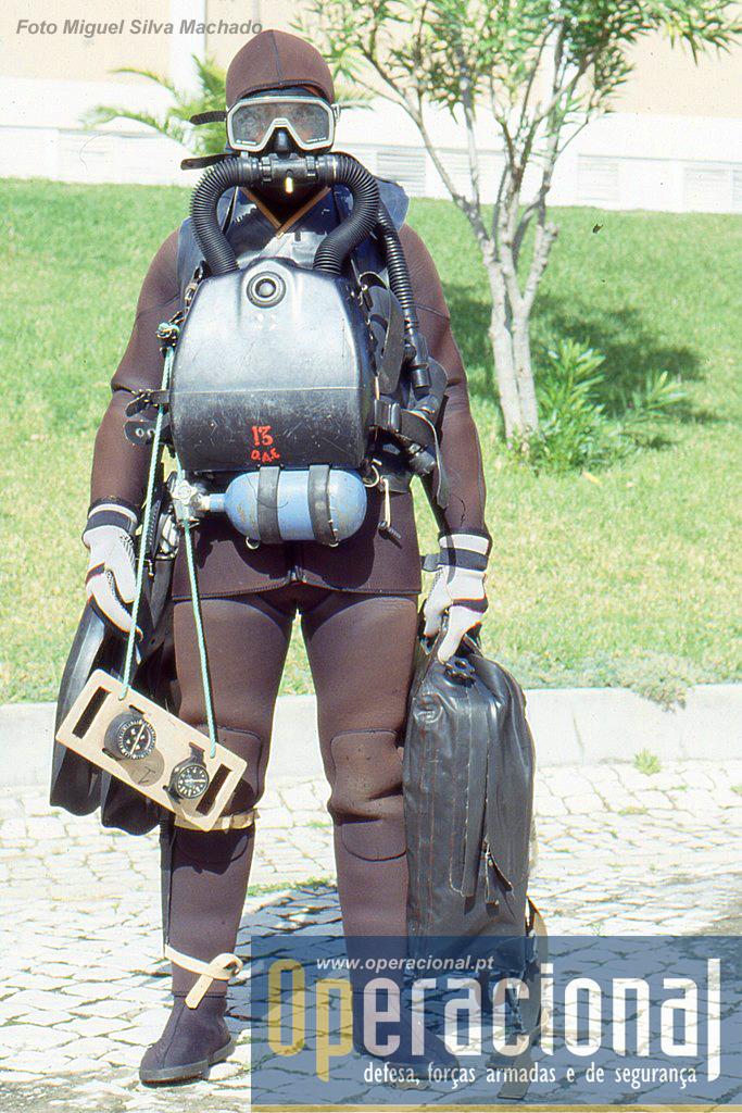 """Apresentação daquilo que era em 1994 o equipamento do DAE para missões de mergulho de combate. Fato neoprene, máscara, barbatanas, equipamento de """"circuito fechado"""" Drager LAR-V, placa de navegação e saco estanque para armamento, explosivos, rações de combate, e equipamento."""