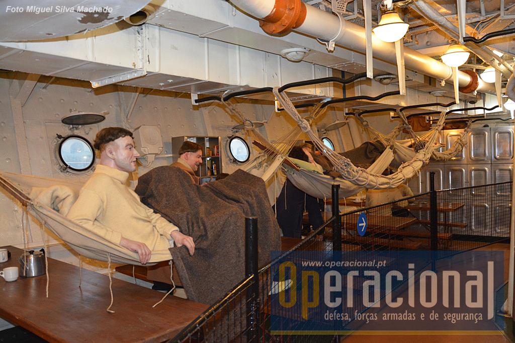 """...quando comparados com os dos marinheiros. Nesta recriação das """"messes de praças"""" durante a campanha do Árctico, estes militares viviam como no tempo de Nelson! Dormiam nestas redes e comiam nas mesas abaixo onde passavam os tempos livres."""