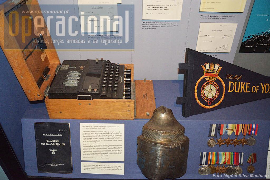 """Uma das curiosidades do museu, uma raríssima máquina """"Enigma"""" (emprestada pelo Museu das Forças Armadas da Noruega). O pedaço de projéctil à direita foi disparado pelo """"Scharnhorst"""", atingiu o HMS Norfolk e matou ou feriu seriamente 12 membros da sua tripulação."""