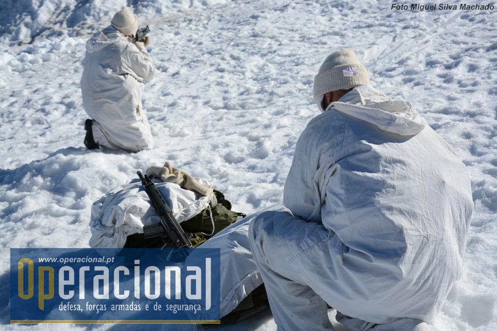 """Um monta segurança e o outro cobre todo o equipamento com cobertura branca, antes de se iniciar um treino de deslocamento na neve com """"raquetes""""."""