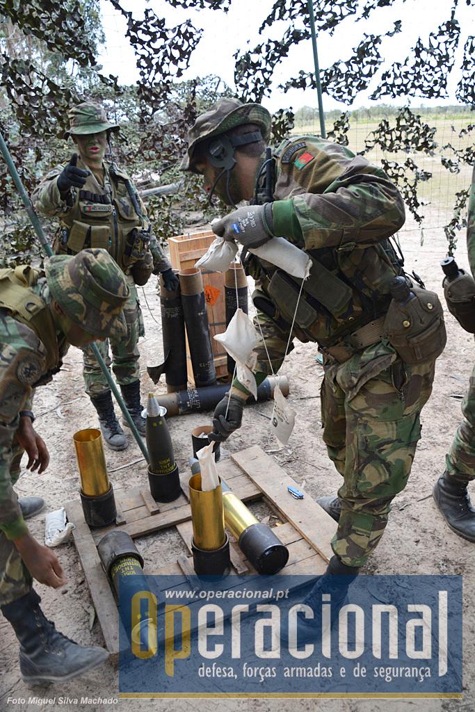 Preparação das munições. As cargas (sacos brancos, numerados) que são retiradas, determinam o alcance do projéctil 105mm (verde) que daqui a pouco irá ser disparado.