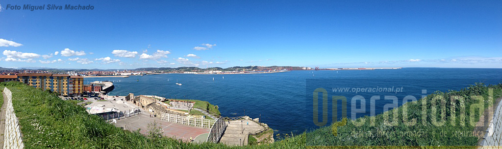 "Ao fundo o Porto de Gijón, e em baixo; à esquerda as ruídas da ""bateria de baixo"" e os equipamentos desportivos."