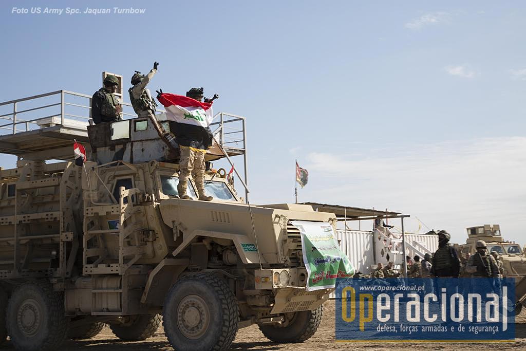"""Militares da 72.ª Brigada do Exército Iraquiano festejam o fim do seu exercício final de validação em Besmayah. Depoiis da formação aqui recebida são considerados aptos a entrar em combate, a realizar """"operações complexas com meios variados e ultrapassar obstáculos como campos de minas ou de natureza urbana - portas, janelas, etc""""."""