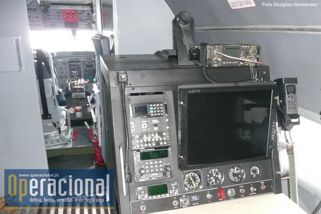 """A consola designada """"estação de inteligência"""", vendo-se a tela para apresentação do FLIR e vários tipos de equipamento de rádio para comunicação ar-ar, ar-terra e varrimento do espectro de frequências. As imagens do FLIR podem ser transmitidas em tempo real aos centros de Comando e Controle da Força Aérea Colombiana."""