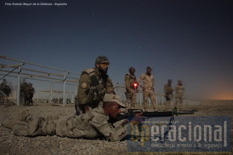 Foto Estado_Maior de Defesa de Espanha com a seguinte legenda: Instructor portugués al lado del soldado iraquí, a quien supervisa su ejercicio de fuego real nocturno con M16.